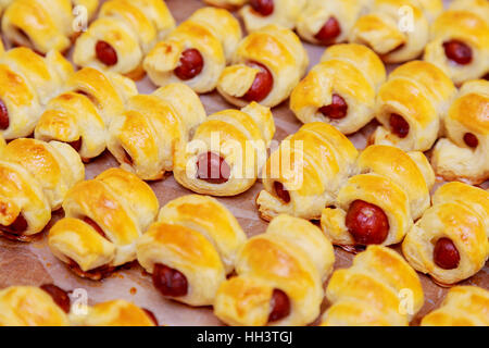 Home made pigs in a blanket. Sausages rolled in croissant dough, baked, cooling on metal rack. - Stock Photo