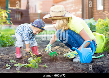Kid and mother planting strawberry seedling into fertile soil outside in garden
