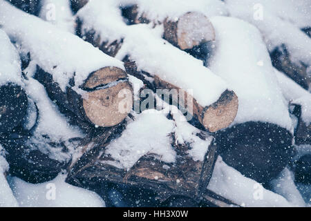 Pile of cut wood logs under white winter snow - Stock Photo
