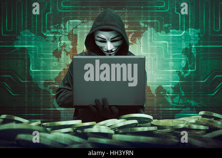 Hooded man with anonymous mask using laptop to hacking bank system security against binary code in background - Stock Photo