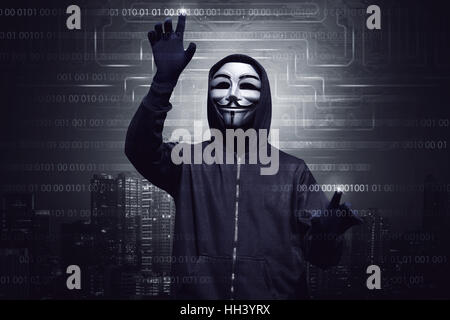 Hooded hacker with mask using virtual screen to hacking system security against digital modern city background - Stock Photo