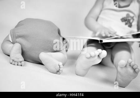 Little girl is reading a book tog her baby brother. Black and white photo with soft focus on their feet. Family - Stock Photo