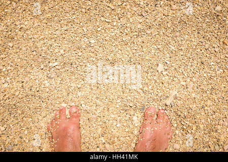 Wet Man feet are standing in sand. Covered with grains of beach sand and sea weed. - Stock Photo
