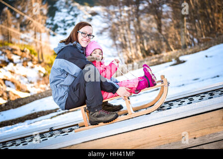 Mother and little child on a ski conveyor on sledge in ski resort school for skiing. - Stock Photo