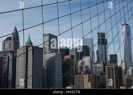 Buildings of the Financial district seen behind the arrangement of suspension ropes from Brooklyn-Bridge. Lower - Stock Photo