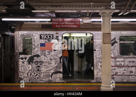 Passengers in a painted subway train during a stop at the waiting platform in a station. New York City, United States - Stock Photo