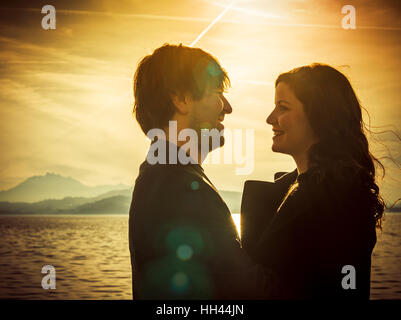 Photo of young adults by the water enjoying the warmth of the sun in the late afternoon in autumn. Heavily filtered - Stock Photo