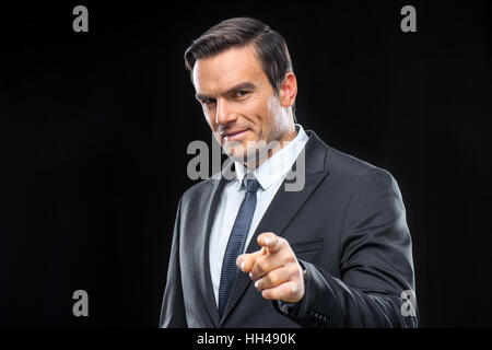 Handsome businessman in suit pointing with finger and smiling at camera - Stock Photo