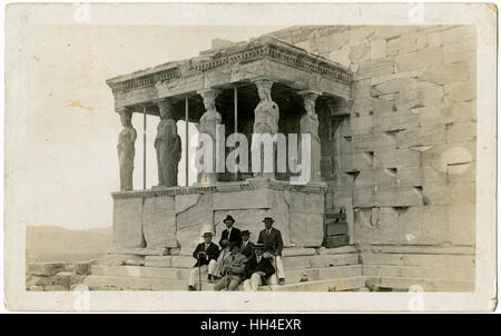 Six Gents sitting beside the Porch of the Caryatids at the Erechtheion or Erechtheum - an ancient Greek temple on - Stock Photo