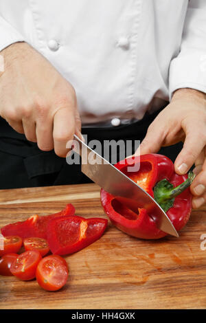Photo of a chef chopping a red bell pepper on a wooden cutting board. - Stock Photo