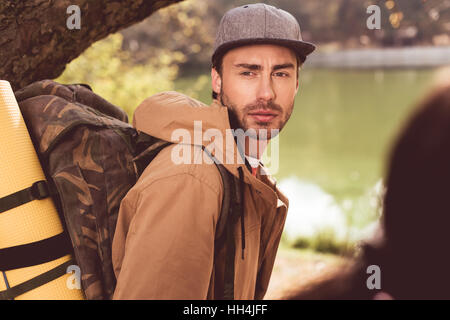 Young bearded man traveler with backpack standing under huge tree near river and looking at blurred woman with ponytail - Stock Photo