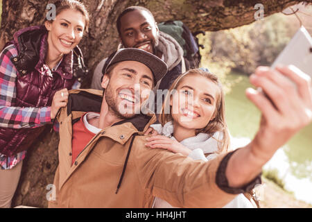 Group of young people standing near huge tree and taking selfie near calm forest river
