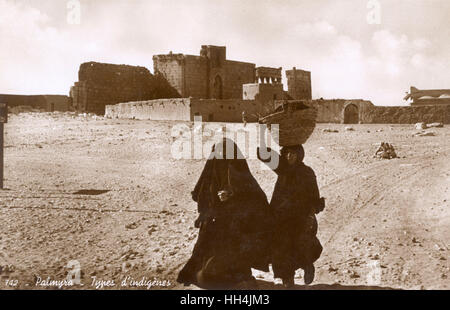 Two native women, one of them carrying a basket on her head, walking from the UNESCO World Heritage Site of Palmyra - Stock Photo