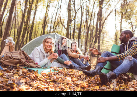 Young friends travelers sitting and talking near tent in autumn forest - Stock Photo