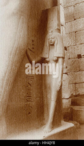 Statue of Queen Nefertari at the side of a sitting statue of Ramesses II at the Luxor Temple, Egypt. The statue - Stock Photo