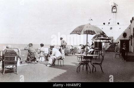 People looking out to sea from the upper terrace of a hacienda style restaurant on the beach front at Playas de - Stock Photo