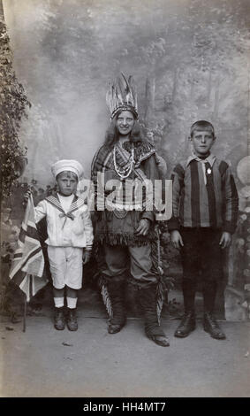 Woman in Native American Indian costume with two boys, one in a sailor suit, the other in a striped sports shirt, - Stock Photo
