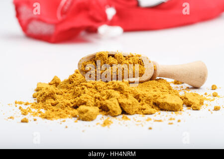 Aromatic yellow color curry powder ingredient on white table with wooden scoop and red fabric bag in background - Stock Photo