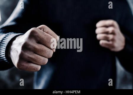closeup of a young caucasian man in casual wear with a threatening gesture, ready to punch or fight with his fists - Stock Photo