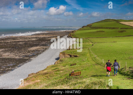 A couple walk along the South West Coast Path, looking towards Westward Ho!, as the sunshine lights up the footpath. - Stock Photo