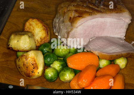 Cooked roast Pork joint with vegetables and potatoes, - Stock Photo