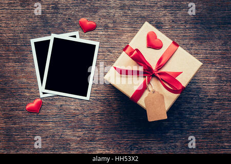 Blank photo frame and gift box with red heart on wood background. - Stock Photo