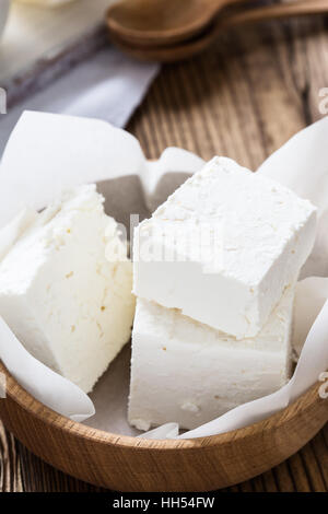 Organic dairy products on rustic wooden table. Farmer cheese in wooden bowl - Stock Photo