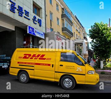 Yellow van of DHL Deutsche Post parcel service with the logo '25 years in Mongolia', Ulaanbaatar, Mongolia Stock Photo