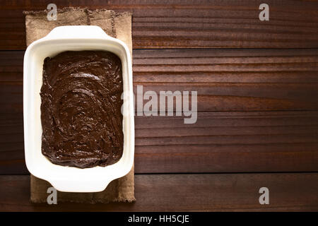 Basic homemade brownie or chocolate cake dough in greased and floured baking pan, photographed overhead with natural - Stock Photo