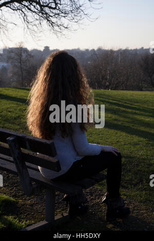 Pensive young woman sitting alone on a bench looking into the distance, in a quiet location with a sky and trees. - Stock Photo