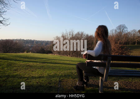 Pensive young woman sitting alone on a bench looking into the distance, in a quiet location with a light sky and - Stock Photo