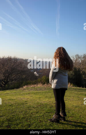 Pensive young woman standing alone on a hilltop looking into the distance, in a quiet location with a light sky - Stock Photo
