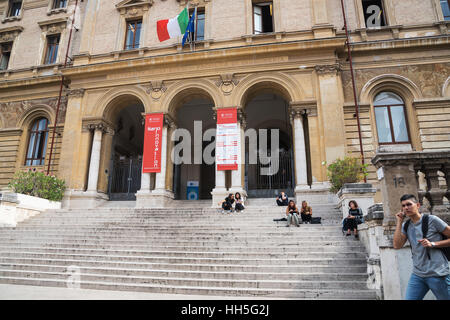 The students sitting on the steps of famous University of Rome, Rome, Italy. - Stock Photo