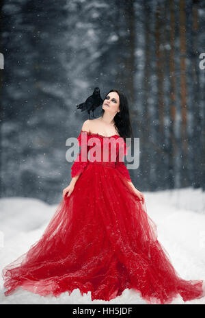 Woman witch in red dress and with raven on her shoulder in snowy forest. Her long dress lying on snow and she looks - Stock Photo
