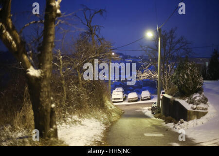A view of parked cars on the street in village covered in snow at sunset. - Stock Photo