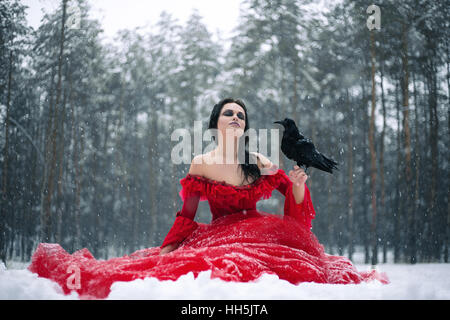 Woman witch in red dress with raven in hand sits on snow in forest.Her long dress lying on snow, and snowflakes - Stock Photo