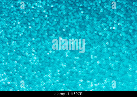 Abstract out of focus blue dots which appear like small bubbles - actually the surface of a piece of textured plastic. - Stock Photo