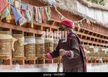 Old Tibetan women turning prayer wheels at a monastery - Stock Photo