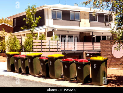 Waste bins lined up outside housing complex in Canberra - Stock Photo