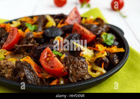 Pieces of roast duck, goose (meat, liver, heart) with vegetables (onion, carrot, tomato), with spices on a cast - Stock Photo