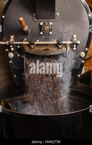 Photo of freshly roasted coffee beans from a large coffee roaster being poured into the cooling cylinder.  Motion - Stock Photo
