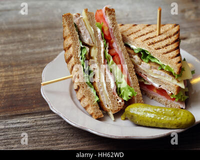 Photo of a club sandwich made with turkey, bacon, ham, tomato, cheese, lettuce, and garnished with a pickle. - Stock Photo