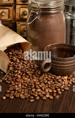 Photo of roasted coffee beans, coffee cup, and ground beans on a wooden table.