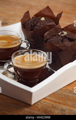 Photo of two moist chocolate muffins and two cups of espresso or coffee resting on a white serving tray. Shallow - Stock Photo
