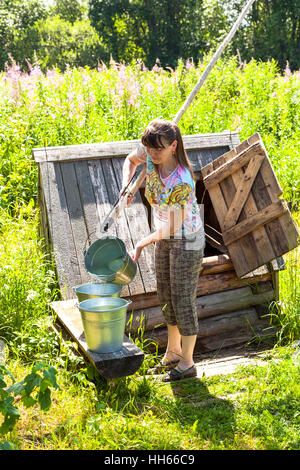 Young attractive woman near the village wooden water well in summer sunny day - Stock Photo