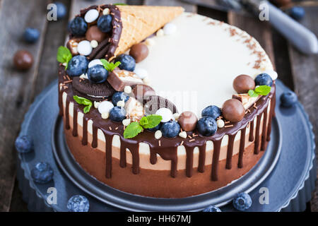 Delicious three chocolate mousse cake decorated with waffle cone, fresh blueberry, mint, candies and frosting - Stock Photo
