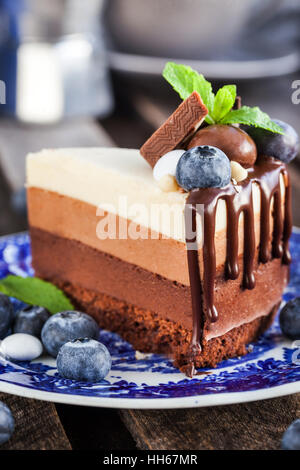 Piece of delicious three chocolate mousse cake decorated with fresh blueberry, mint and candies - Stock Photo