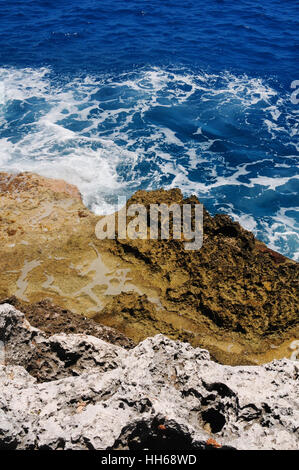 Rugged coral rocks and reef cliffs on the shores of Grand Cayman, Cayman Islands. Turquoise waters of Caribbean - Stock Photo