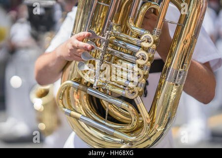 Tuba player in a military or marching band playing during a parade or festival on a sunny day. Wearing a white uniform - Stock Photo