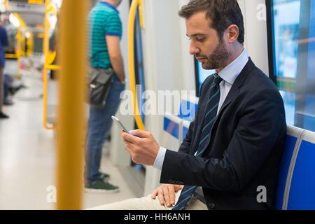 Businessman commuter traveling on the metro underground - Stock Photo
